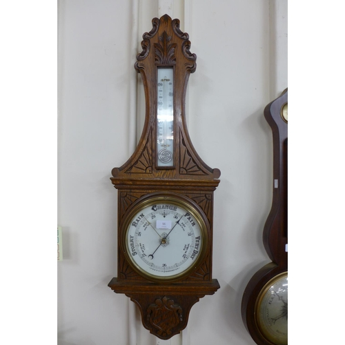 78 - A Victorian carved oak aneroid barometer...