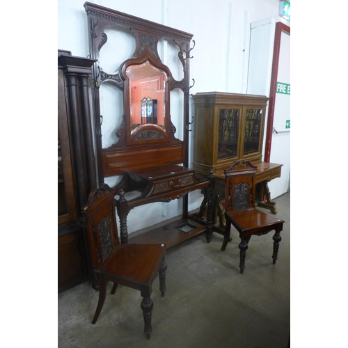 53 - A Victorian mahogany hallstand and matching pair of hall chairs...