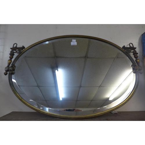 31 - An Edward VII brass framed oval mirror...