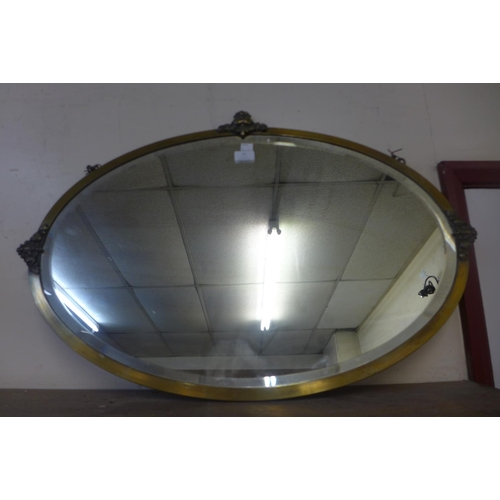 32 - An Edward VII brass framed oval mirror...