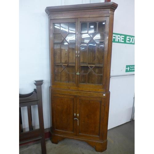 59 - A George III oak corner cabinet...