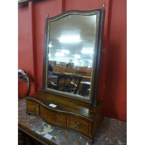 82 - A George III mahogany and parcel gilt three drawer serpentine front toilet mirror...