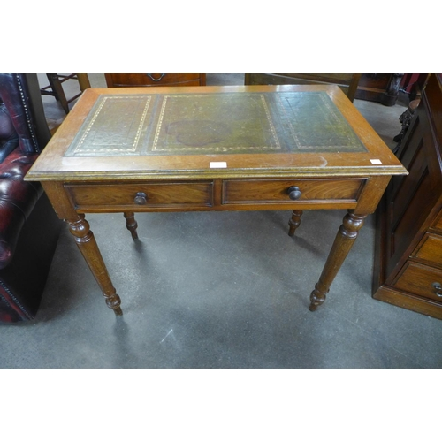 114 - A Victorian oak and leather topped two drawer writing table...