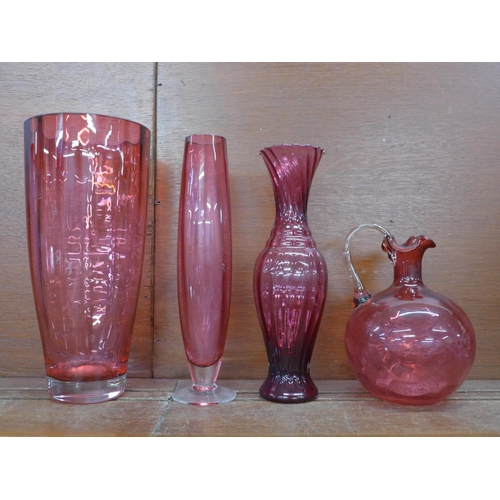613 - Four items of cranberry glass; large vase, 28cm, two other vases and a decanter, lacking stopper...