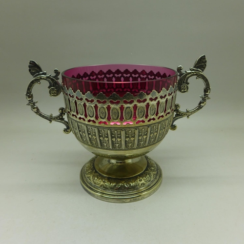 640 - A pierced WMF two handled sugar basket with cranberry glass liner, circa 1905...