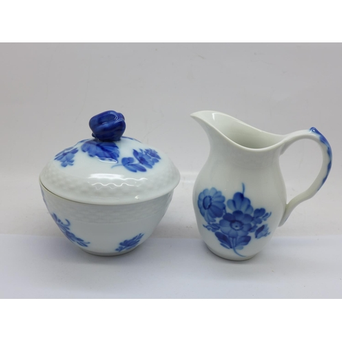 664 - A Royal Copenhagen cream jug and sucrier decorated with blue flowers and with basket weave moulded r...