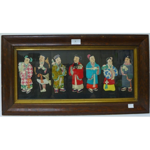 9 - A Japanese textile depicting seven figures, framed, 34 x 62cms...