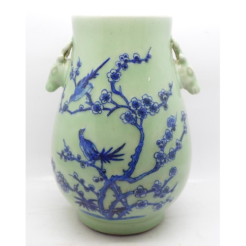 614 - A Chinese celadon vase decorated with two birds in a Prunus bush, 21.5cm...