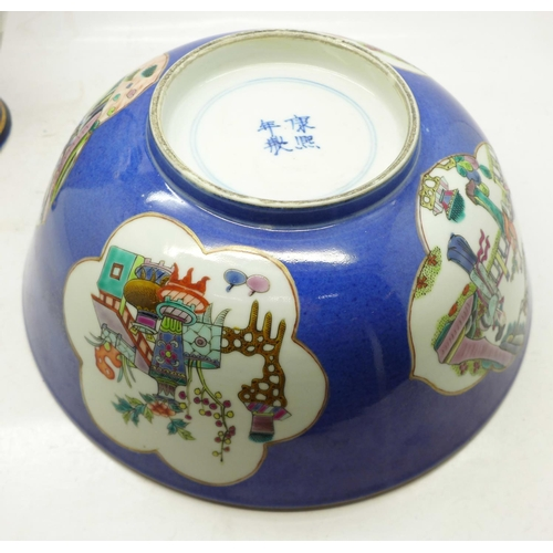 621 - A Chinese blue ground famille rose hand painted porcelain bowl with panels of figures, flowers and l...