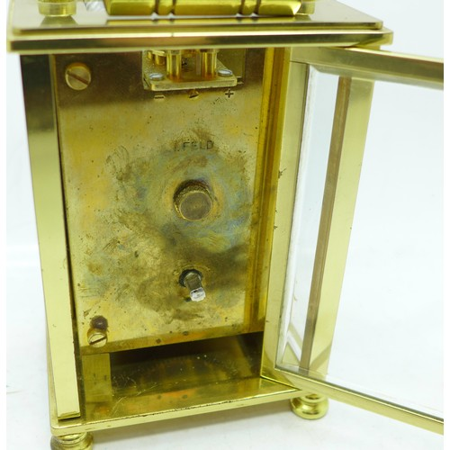 639 - An English brass cased carriage clock with key, the dial marked Dominion...