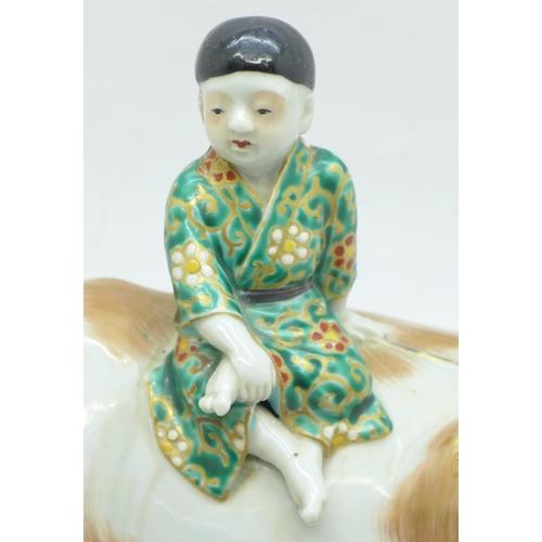 645 - A Meiji period Arita porcelain boy and buffalo, buffalo a/f (horn missing)...