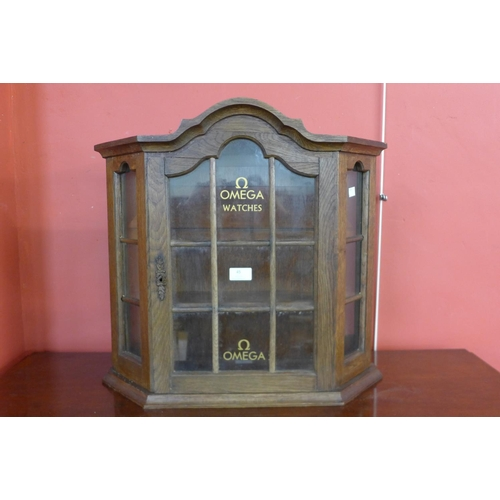 45 - A small oak cabinet, bearing Omega Watches inscription to door...