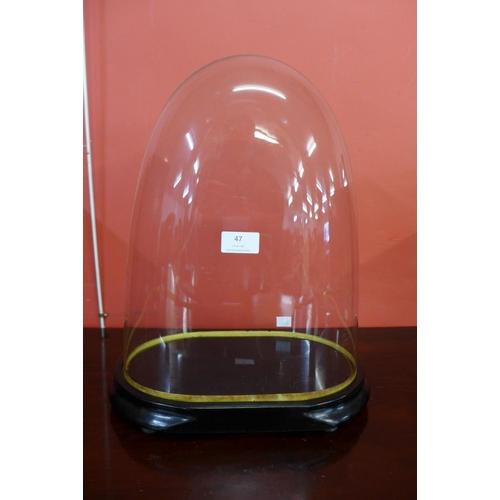 47 - A glass clock dome on ebonised base...