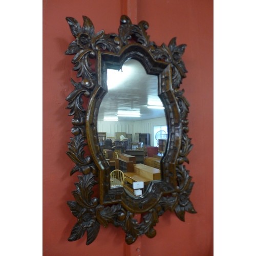 61 - A Baroque Revival carved oak framed mirror...