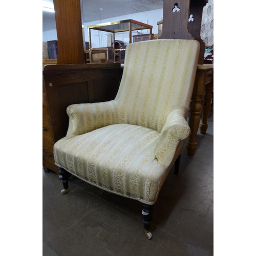 76 - A Victorian ebonised and upholstered armchair...