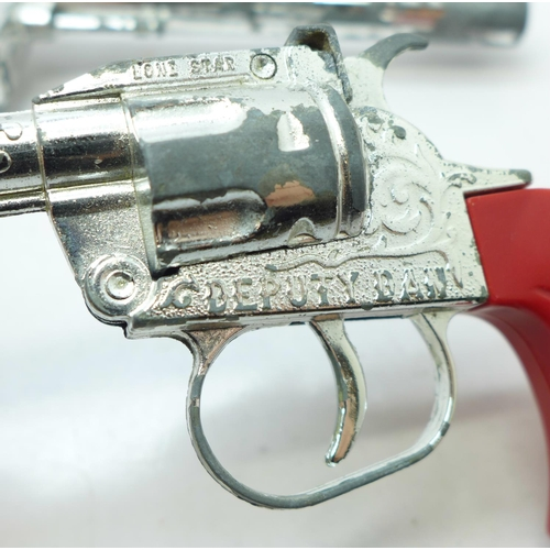 656 - Three cap guns, Lone Star and Crescent Toys, a pair of toy handcuffs and a holster...