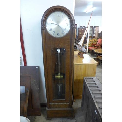 38a - An early 20th Century oak electric longcase clock...
