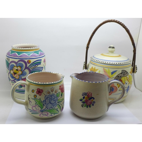 617 - Four items of Poole pottery; a biscuit barrel, vase and two jugs, one jug crazed...