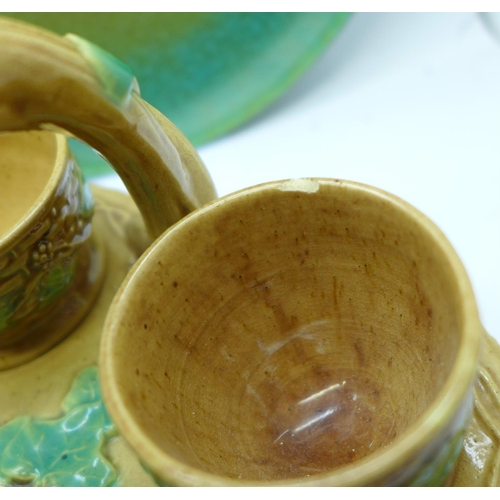 646 - A Majolica triple fish vase, a/f, Majolica egg cups and stand, two Royal Doulton plates with green a...