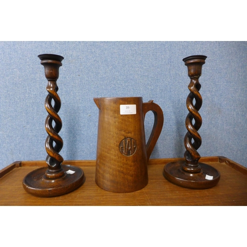 39 - A pair of oak barleytwist candlesticks, 31cms and a treen jug...