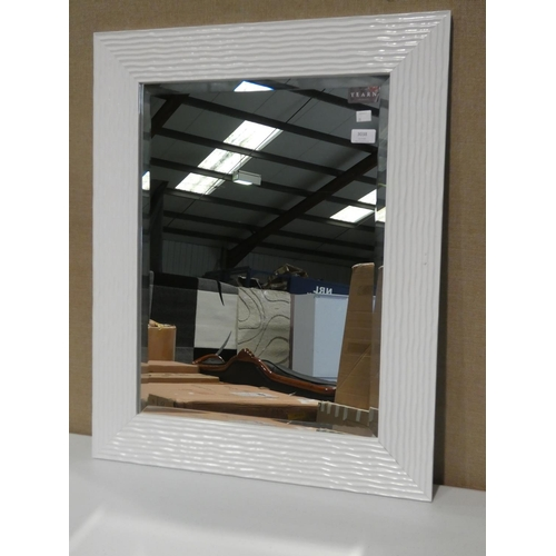3038 - A white ripple gloss framed wall mirror (H78 x W62cm) * this lot is subject to VAT...