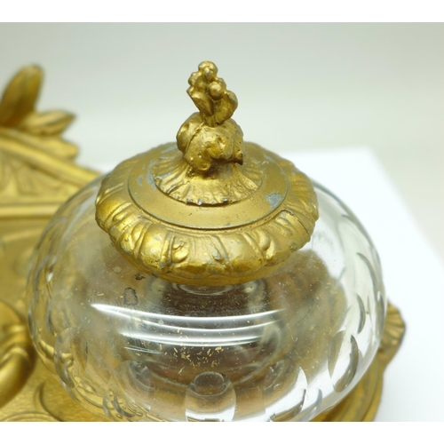 658 - A c.1900 metal inkstand with two glass inkwells, one top a/f, mounted with a bust marked Cornelle...