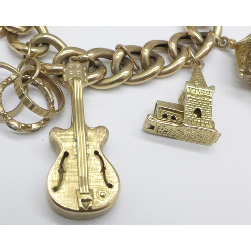 1053 - A 9ct gold charm bracelet with seven hallmarked 9ct gold charms including a guitar, total weight 37....