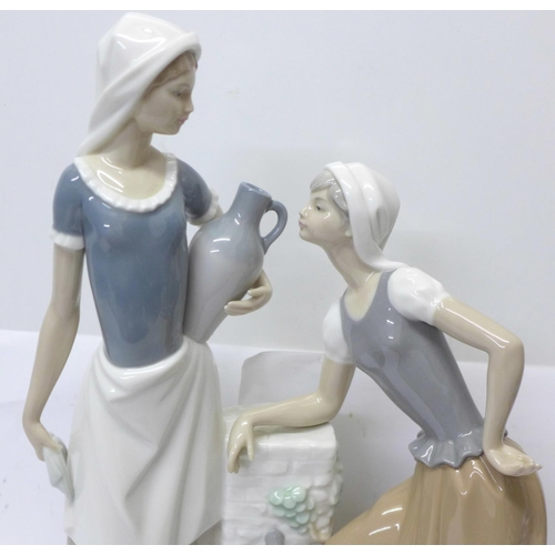 603 - A large Nao by Lladro porcelain figure, Ladies at the Well Talking, model no. 02000178, designer Fra...