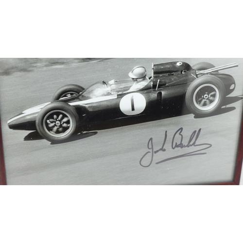 620 - A framed signed photograph of Jack Brabham...