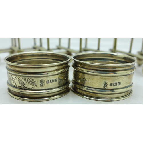 640 - Two silver napkin rings, 18g, and a silver plated extending toast rack...