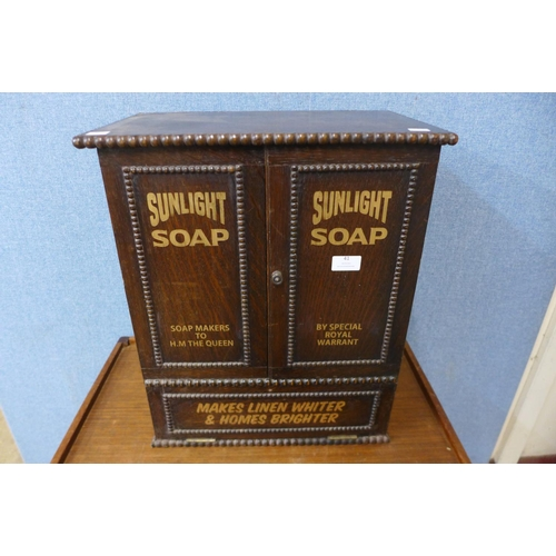 51 - An oak table top shop cabinet, bearing Sunlight Soap inscription to doors...