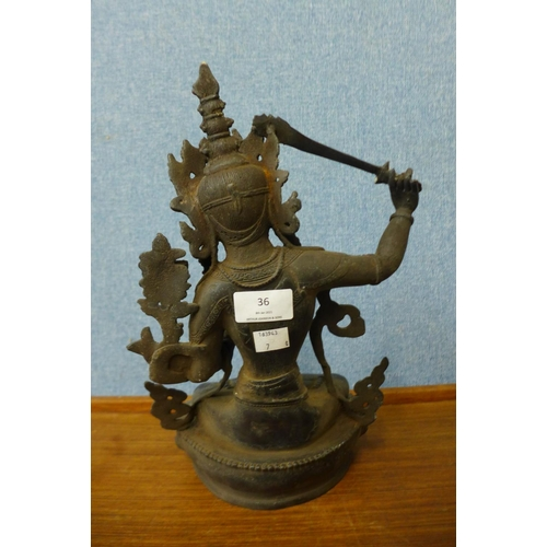36 - An oriental bronzed figure of a seated deity, 33cms h...