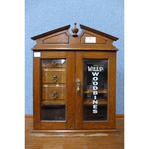 52 - An oak smokers cabinet, bearing Wills Woodbines inscription...