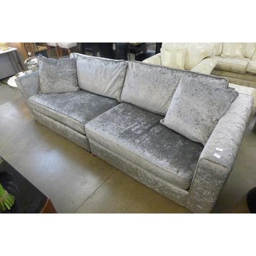 1345 - A grey velvet four seater sofa...