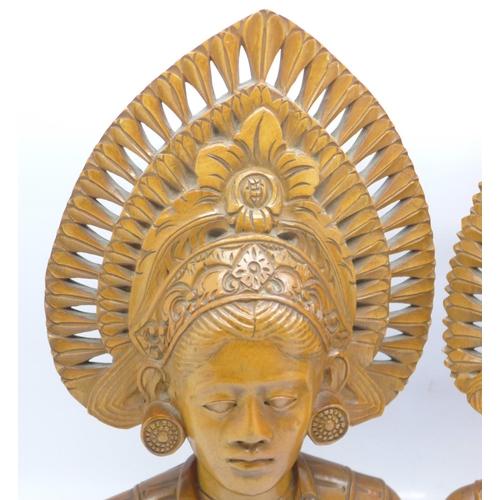 603 - Two carved wooden busts, Djanger dancers, Bali, 24cm, one cracked...