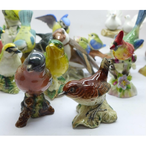 649 - A collection of twenty bird figures including Beswick and a novelty penguin salt and pepper pair, (1...