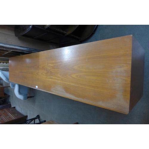 228a - A Danish teak sliding three door sideboard...