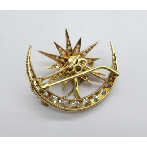 1291 - A yellow metal set diamond starburst crescent brooch, set with 54 diamonds, the centre stone 0.75car...