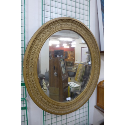 65 - A Victorian gilt gesso framed oval mirror, 84 x 75cms...