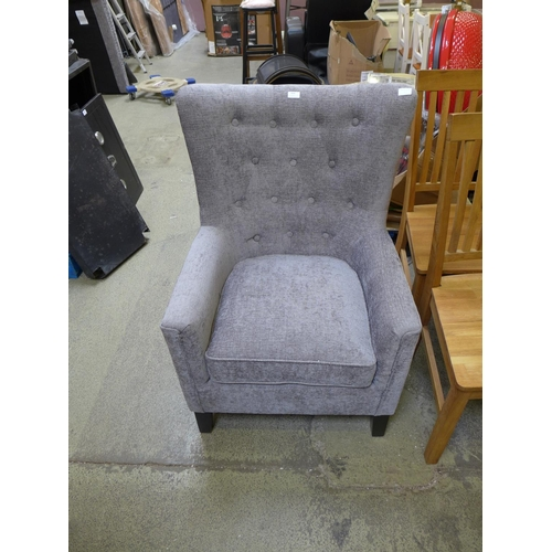 A silver wingback upholstered armchair