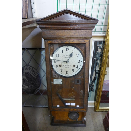 30 - An oak wall hanging clocking in machine, Time Recorders (Leeds Ltd.)
