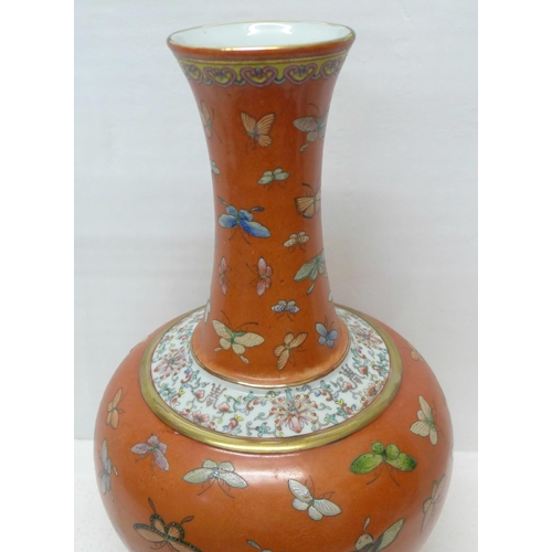 789 - A Chinese coral red ground Famille Rose 'butterfly vase', bulbous body and tall, waisted neck, decor...