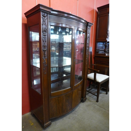 22 - A Hepplewhite Revival carved mahogany two door bow front side cabinet