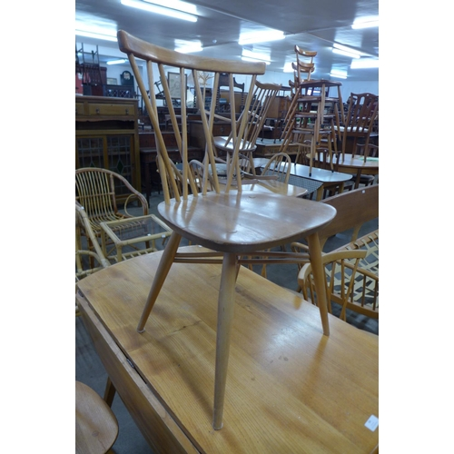 64 - An Ercol Blonde elm and beech Windsor drop-leaf table and four 376 model candlestick back chairs