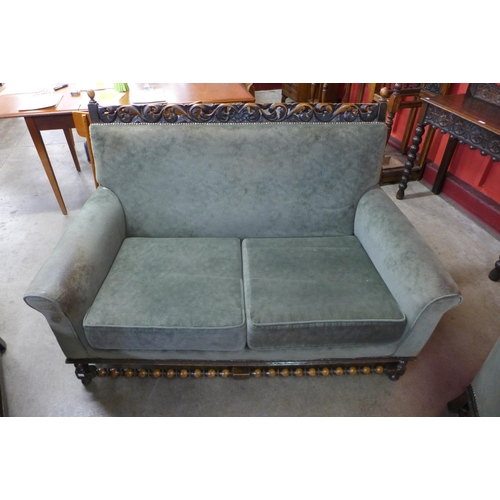7 - An early 20th Century carved oak and green fabric upholstered three piece lounge suite, attributed t...