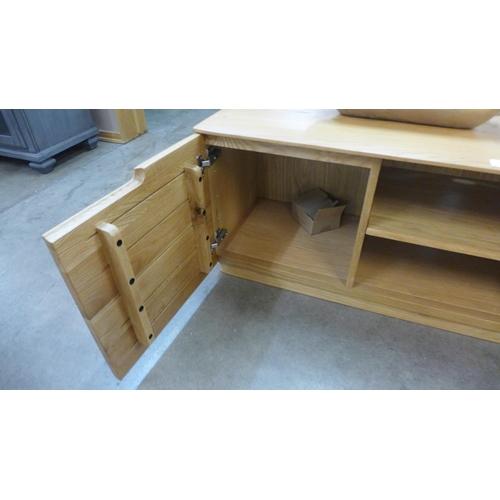 1302 - An oak designer two door TV cabinet ( one interior shelf missing)