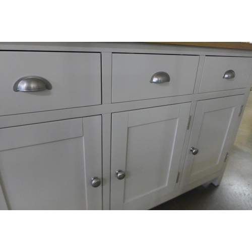 1442 - A Rutland truffle painted oak three door sideboard. repaired to left hand side * this lot is subject...