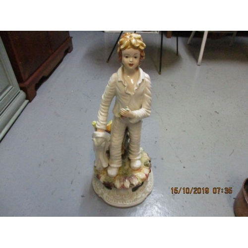 12 - A large Capodimonte figurine 50cm high. A young boy carrying his coat in one hand and food in the ot...