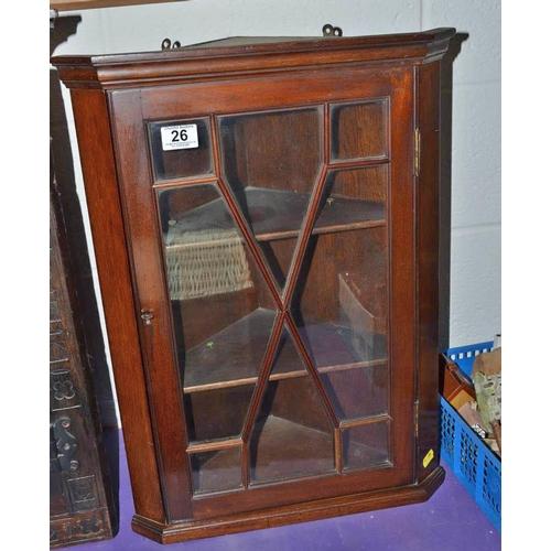26 - An antique wooden glazed corner cabinet...