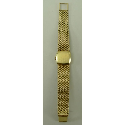 814 - A lady's 18ct gold Omega wristwatch, the square gold face with baton numerals, on a woven gold strap...